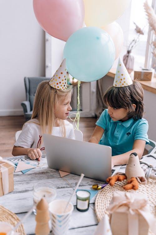 2 Kinder mit Party Mützen und Laptop